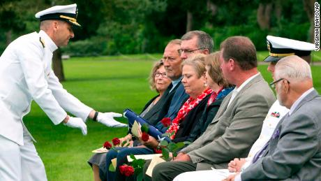 A US Navy sailor performs a handover ceremony of the flag from WWII sailor Julius Pieper to family member Linda Suitor during a reburial service at the Normandy American Cemetery on June 19.
