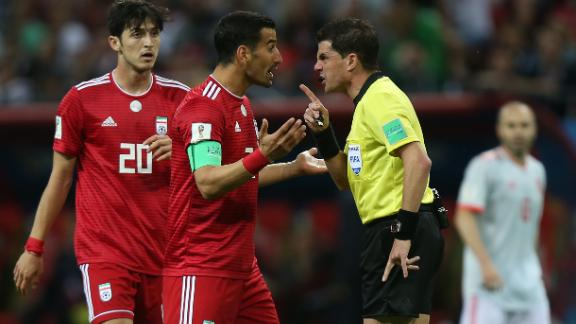 Referee Andres Cunha speaks with Iranian midfielder Ehsan Hajsafi during the match.