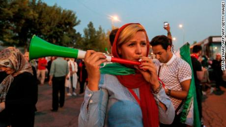 An Iranian woman blows a vuvuzela as she arrives outside Azadi stadium in the capital Tehran on June 20, 2018, to attend a screening of the Russia 2018 World Cup Group B football match between Iran and Spain. (Photo by ATTA KENARE / AFP)        (Photo credit should read ATTA KENARE/AFP/Getty Images)