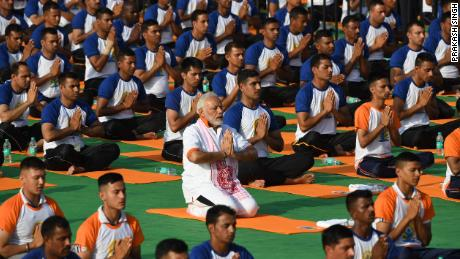 Indian Prime Minister Narendra Modi participates in a mass yoga session along with other practitioners to mark International Yoga Day at the Forest Research Institute (FRI) in Dehradun on June 21, 2018.