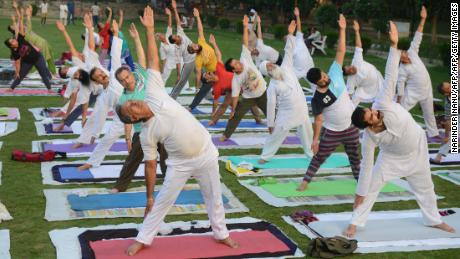 Indian yoga practitioners take part in a yoga session ahead of International Yoga Day at a park in Amritsar on June 20, 2018.