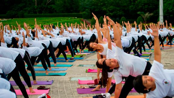 People participate in an outdoor yoga session at a park in Yangon, Myanmar to celebrate the International Yoga Day.