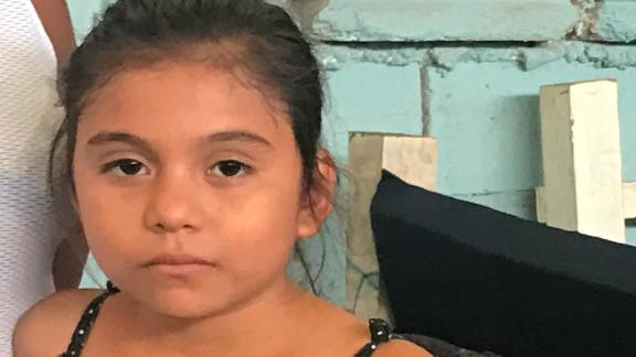 Kensi Hernandez stands with her mom, Ana, by their bed in a shelter in Tapachula, Mexico.