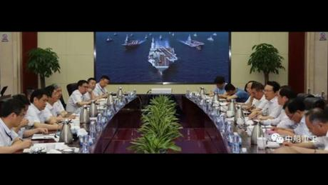 Screen shot from Chinese media shows a conference of the at the No.701 Research Institute of China Shipbuilding Industry Corporation with picture in background of China's two current ski-jump carriers flanking a larger ship with a flat deck