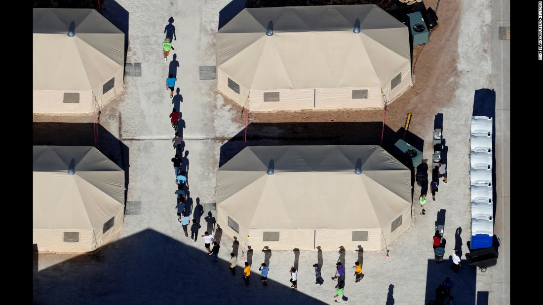 "Immigrant children who have been separated from their families walk between tents at a temporary shelter in Tornillo, Texas, on Monday, June 18. <a href=""https://www.cnn.com/2018/06/20/politics/unaccompanied-children-centers/index.html"" target=""_blank"">Related story: A look inside the places where child migrants are held</a>"