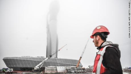 A worker looks at the control tower of a new airport under construction in Istanbul on April 13.