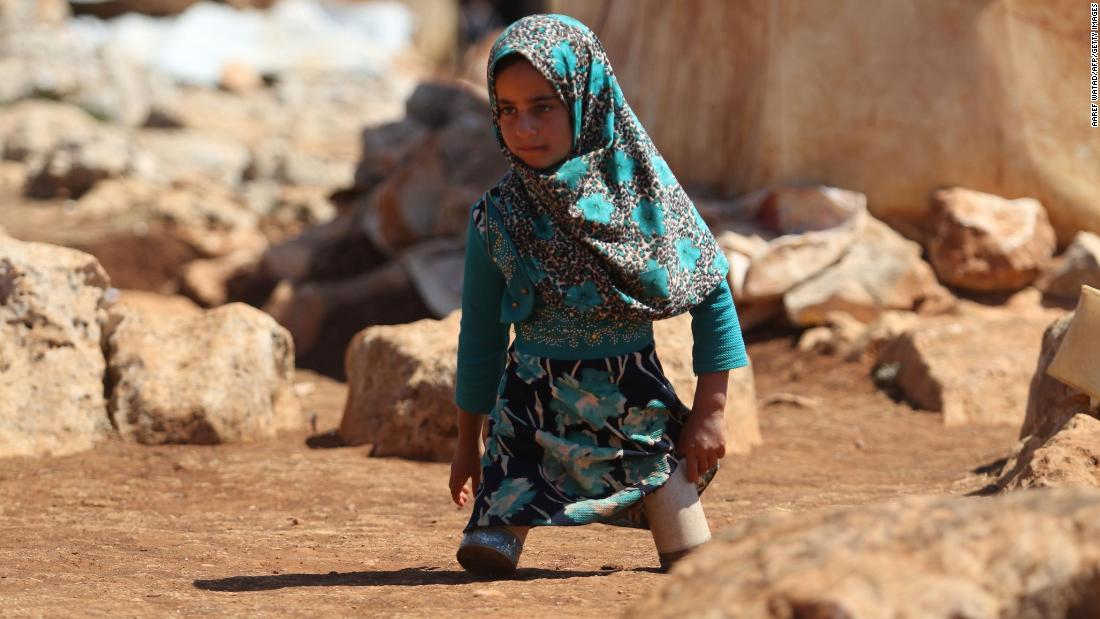 Maya Mohammad Ali Merhi walks at a camp for displaced people in Idlib, Syria, on Wednesday, June 20. The 8-year-old was born without lower limbs. Her father was unable to afford real prosthetics, so he made some for her out of tin cans.