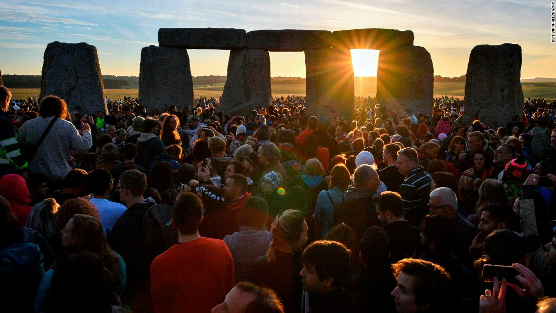 "Sunlight filters through Stonehenge as people gather to celebrate the <a href=""https://www.cnn.com/travel/article/summer-solstice-world-traditions/index.html"" target=""_blank"">summer solstice</a> in Wiltshire, England, on Thursday, June 21."