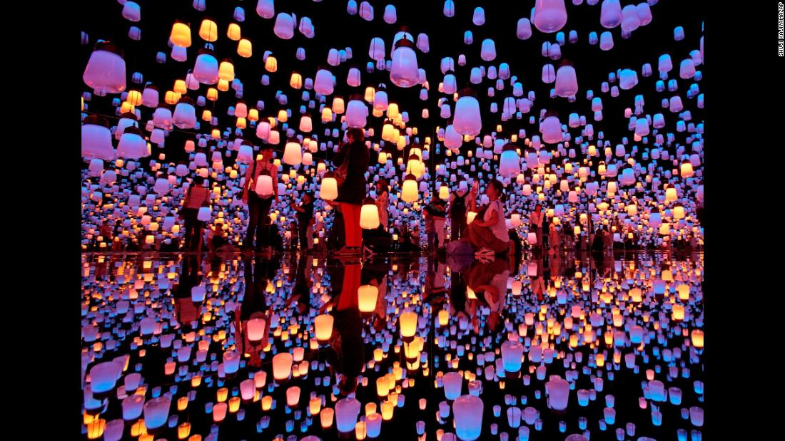"Visitors walk through ""Forest of Resonating Lamps,"" an installation at the Mori Building Digital Art Museum in Tokyo, on Thursday, June 21. <a href=""http://www.cnn.com/2018/06/14/world/gallery/week-in-photos-0615/index.html"" target=""_blank"">See last week in 22 photos</a>"