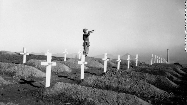 "On December 13, 1950 during memorial services at the First Marine cemetery in Hungnam, Korea, Corporal Charles Price sounds ""Taps"" over the graves of fallen U.S. Marines following the division's heroic break-out from Chosin Reservoir. (Photo by © CORBIS/Corbis via Getty Images)"