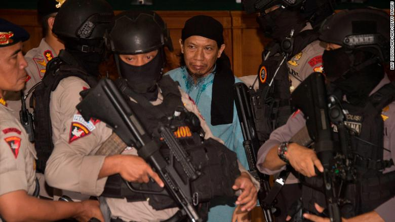 Indonesian anti-terror police officers escort Aman Abdurrahman (C), who masterminded a 2016 gun and suicide attack in the capital Jakarta that left four attackers and four civilians dead, after hearing the judges' verdict at a South Jakarta court in Jakarta on June 22, 2018. - Indonesian cleric Aman Abdurrahman was sentenced to death over his role in a 2016 Islamic State terror attack that saw a suicide bomber blow himself up at a Jakarta Starbucks cafe. (Photo by BAY ISMOYO / AFP)        (Photo credit should read BAY ISMOYO/AFP/Getty Images)