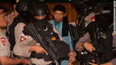 Indonesian anti-terror police officers escort Aman Abdurrahman after the judges' verdict.