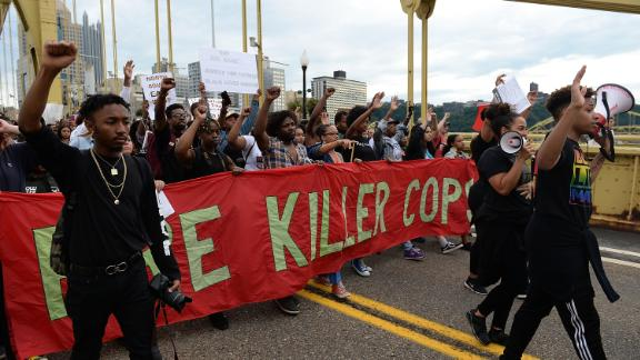 Protesters cross the Roberto Clemente Bridge Friday following the death of 17-year-old Antwon Rose.