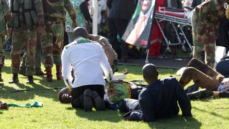Injured people are attended to as they lay on the ground following an explosion at a Zanu pf rally in Bulawayo, Saturday, June, 23, 2018.  An explosion rocked a stadium where Zimbabwe's president was addressing a campaign rally on Saturday, with state media calling it an assassination attempt but saying he was not hurt and was evacuated from the scene. Witnesses said several people were injured, including a vice president. (AP Photo)
