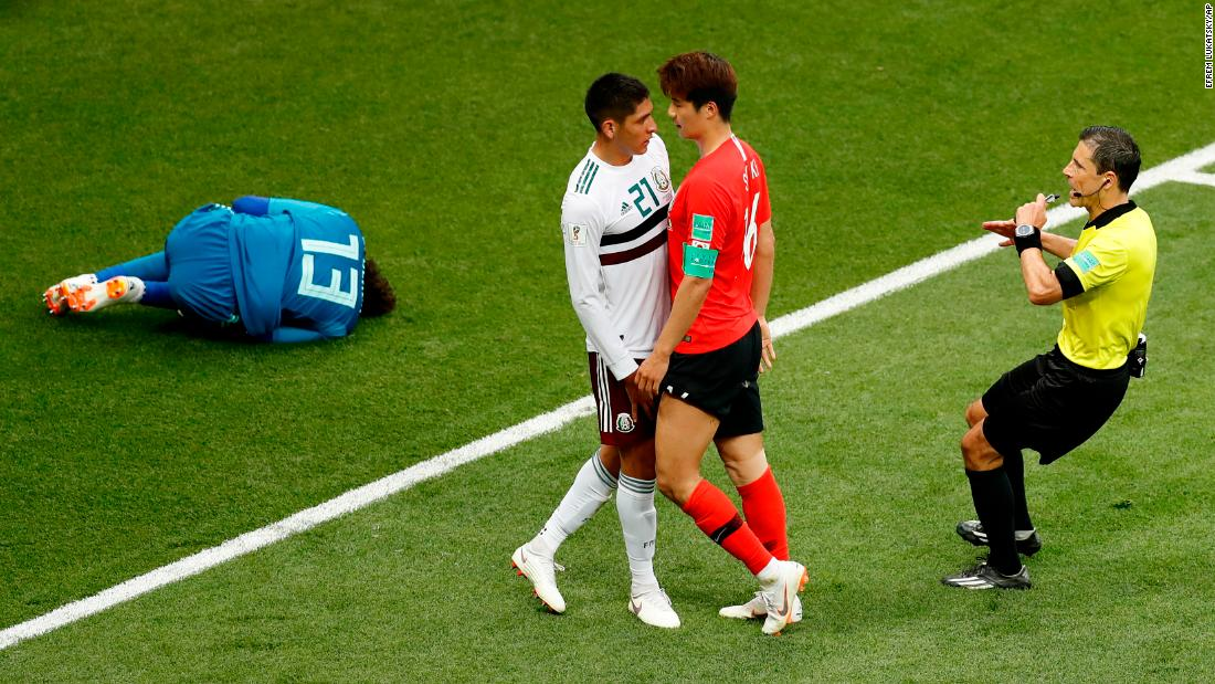 Mexico's Edson Álvarez and South Korea's Ki Sung-yueng argue as Mexican goalkeeper Guillermo Ochoa lies in pain on Saturday, June 23.