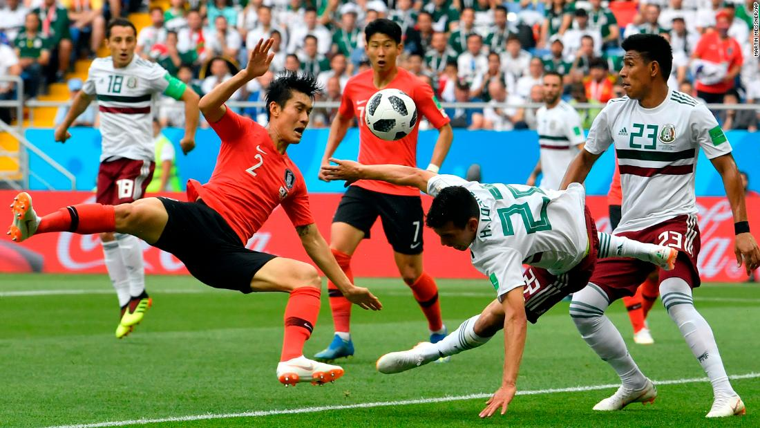 South Korea's Lee Yong, left, duels for the ball with Mexico's Hirving Lozano.