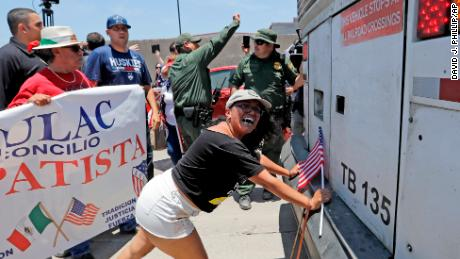 Demonstrator Martha Mercado tries to stop a bus with immigrant children onboard during a protest outside the U.S. Border Patrol Central Processing Center Saturday, June 23, 2018, in McAllen, Texas. Extra law enforcement officials were called in to help control the scene and allow the bus to move. (AP Photo/David J. Phillip)