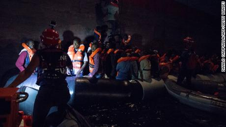 Migrants board the Danish Maersk cargo ship in darkness on Friday.