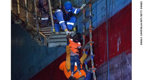 Migrants board the Maersk cargo ship on Friday.