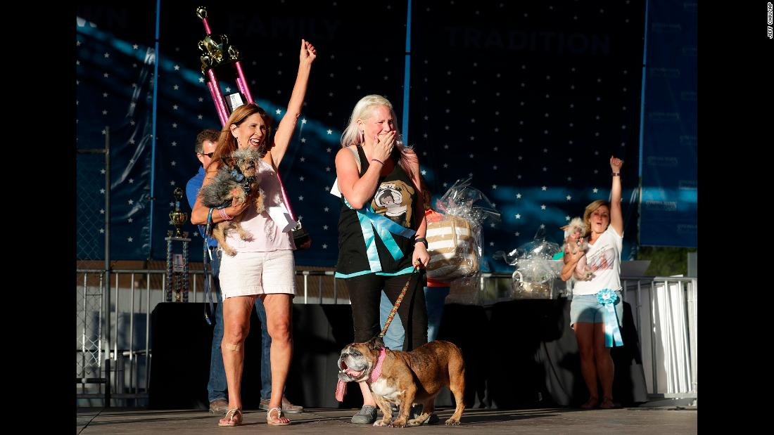 Brainard, center, celebrates after Zsa Zsa, bottom, is announced the winner of the 30th World's Ugliest Dog Contest. Also pictured are Yvonne Morones, left, and Linda Elmquist, holding their less-ugly dogs Scamp and Josie, who came in second and third, respectively.