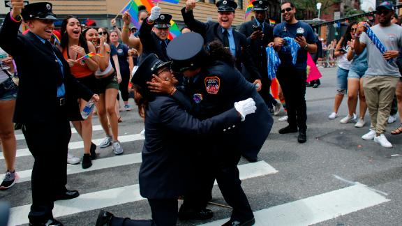 Members of the New York City Fire Department cheer as EMT Trudy Bermudez and paramedic Tayreen Bonilla get engaged at the annual Pride Parade