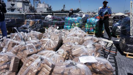 Coast Guard personel stand aboard the USS Boutwell while officials unload bails of cocaine caught at sea while on deployment on April 16, 2015 at Naval Base San Diego in San Diego, California.