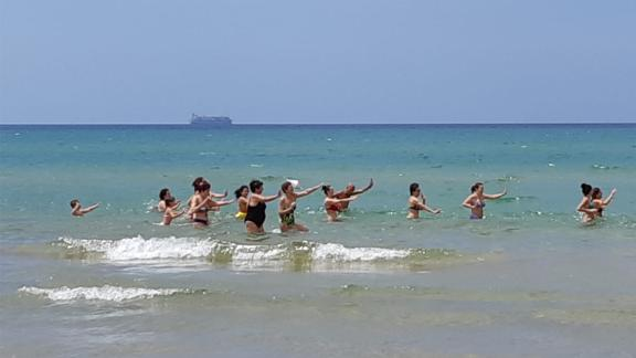 Beachgoers enjoy a Zumba class in Pozzallo, Sicily, as the Maersk migrant ship sits in the background.