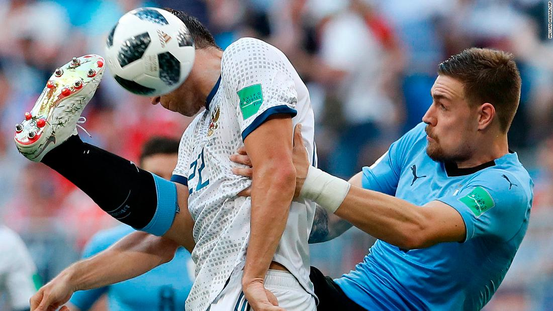 Russia's Artem Dzyuba, in white, competes with Uruguay's Sebastian Coates during Uruguay's 3-0 victory on Monday. Uruguay won all three of its matches in the group stage. This was Russia's first loss.
