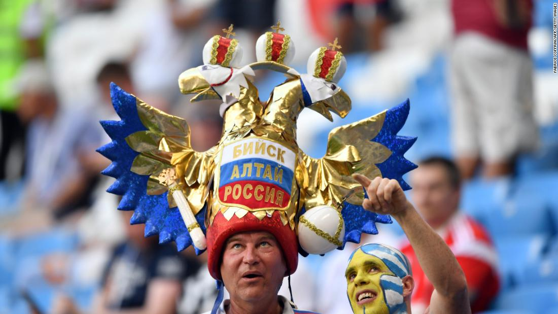 A Uruguay fan, right, poses with a Russia fan before the match.