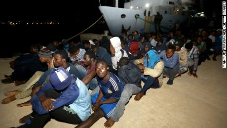 Migrants wait at a naval base in Tripoli, after being rescued in the Mediterranean on June 24, 2018.