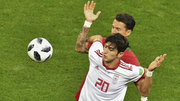 Iranian forward Sardar Azmoun shields the ball from Portuguese defender Jose Fonte.