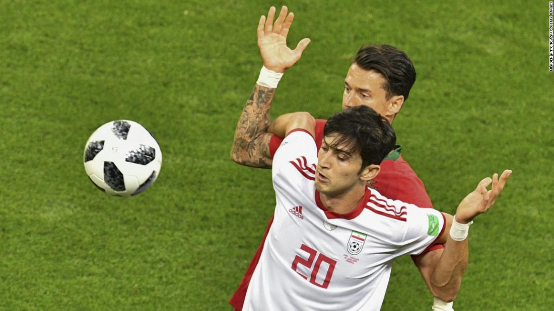 Iranian forward Sardar Azmoun shields the ball from Portuguese defender Jose Fonte.