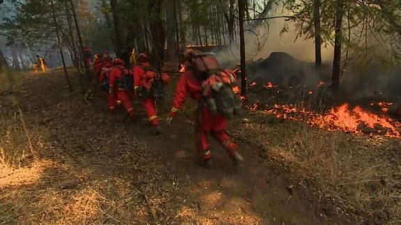 Firefighters on the ground take on the growing flames.