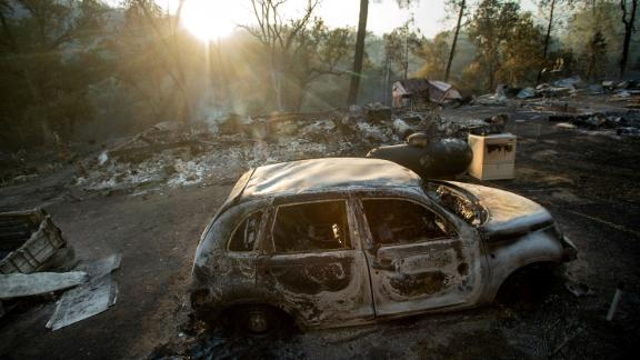 A vehicle scorched by a wildfire remains in a clearing on Wolf Creek Road near Clearlake Oaks.
