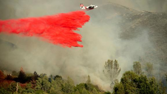 An air tanker drops retardant on a wildfire burning above the Spring Lakes community.