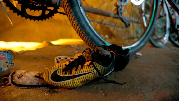 Soccer shoes are left next to bikes from the missing boys at the entrance of a cave in northern Thailand.