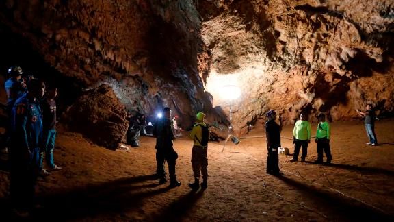 Rescue teams gather Monday in a deep cave where the group of boys went missing.