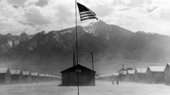 CALIFORNIA, UNITED STATES - FEBRUARY 02:  Incongruous American flag flying over scene of two children running on dusty wind swept grounds of bleak Manzanar relocation camp, one of several such camps housing forcebly relocated Japanese nationals and American citizens of Japanese descent during WW