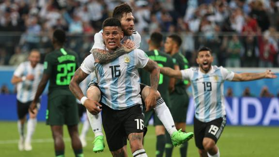 Argentina star Lionel Messi rides on the back of Marcos Rojo after Rojo