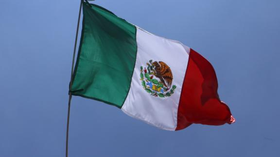 """Mexico's presidential candidate Ricardo Anaya (C), standing for the """"Mexico al Frente"""" coalition of the PAN-PRD-Movimiento Ciudadano parties, waves a Mexican national flag during the final rally of his campaign at Angel de la Independencia monument in Mexico City, on June 24, 2018, ahead of the July 1 presidential election. (Photo by ULISES RUIZ / AFP)        (Photo credit should read ULISES RUIZ/AFP/Getty Images)"""