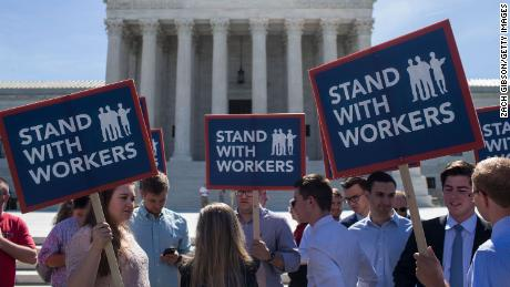 WASHINGTON, DC - JUNE 25: Demonstrators hold signs in front of the U.S. Supreme Court on June 25, 2018 in Washington, DC. The high court is expected to issue decisions in six remaining cases, including the travel ban, public sector unions and redistricting, ahead of their end-of-June deadline this week.  (Photo by Zach Gibson/Getty Images)