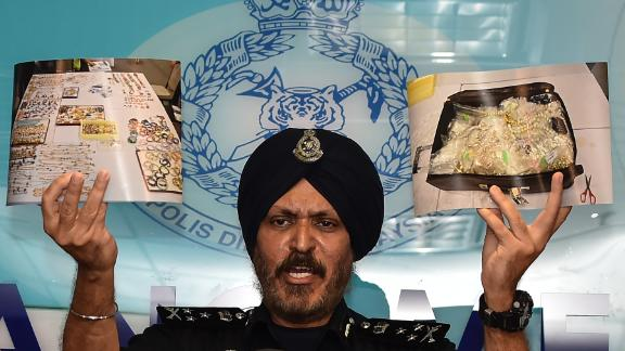 Malaysian Police Commercial Crime Investigation Department (CCID) Director Amar Singh shows pictures of seized items from Najib's properties while addressing media in Kuala Lumpur on June 27.