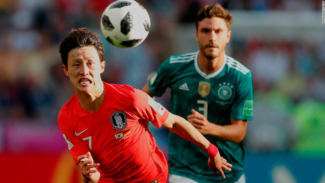 South Korea's Lee Jae-sung, left, chases down a ball with Germany's Jonas Hector.