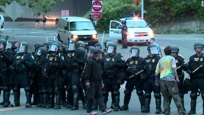 A couple protesters stand Thursday morning near officers in riot gear as they block an entrance to the Portland ICE facility.