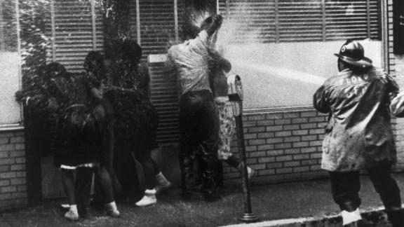 (Original Caption) Firemen bear in on a group of African Americans who sought shelter in a doorway as hoses and dogs were used in routing anti-segregation demonstrators.