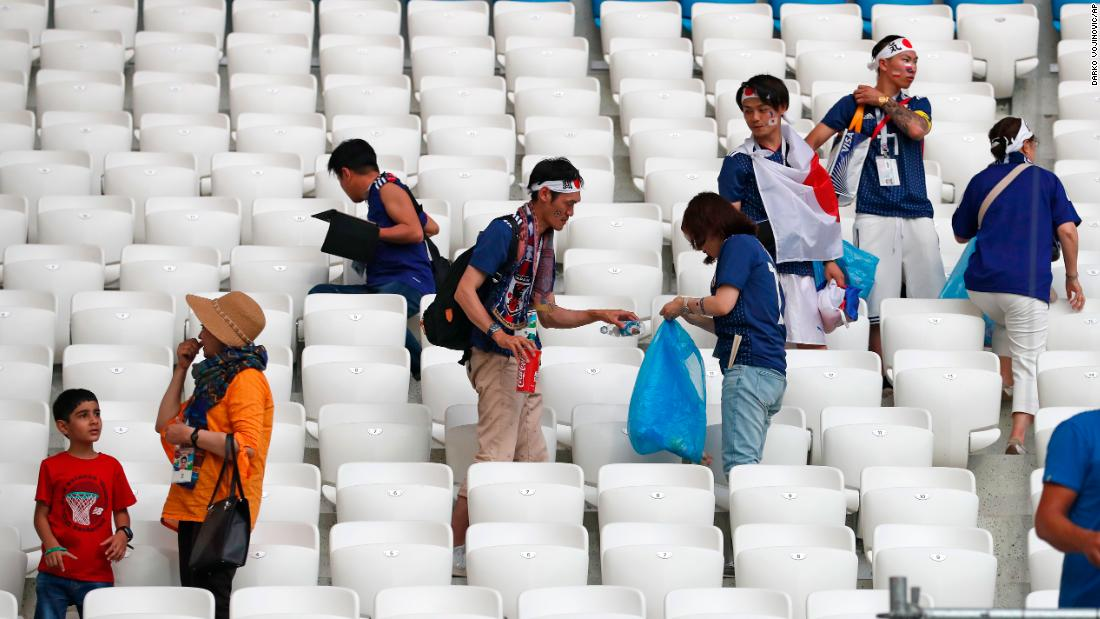 Japan supporters clear litter from the stands after the match.