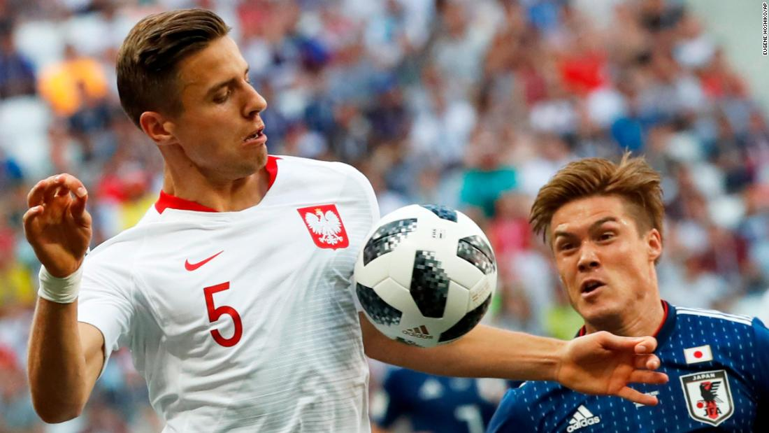 Poland's Jan Bednarek, left, competes for the ball with Japan's Gotoku Sakai on Thursday. Poland won 1-0, its first win of the tournament, but Japan advanced to the next round.