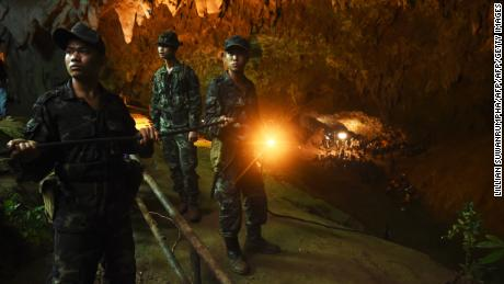 Thai soldiers relay electric cable deep into the entrance of the Tham Luang Nang Non cave network.