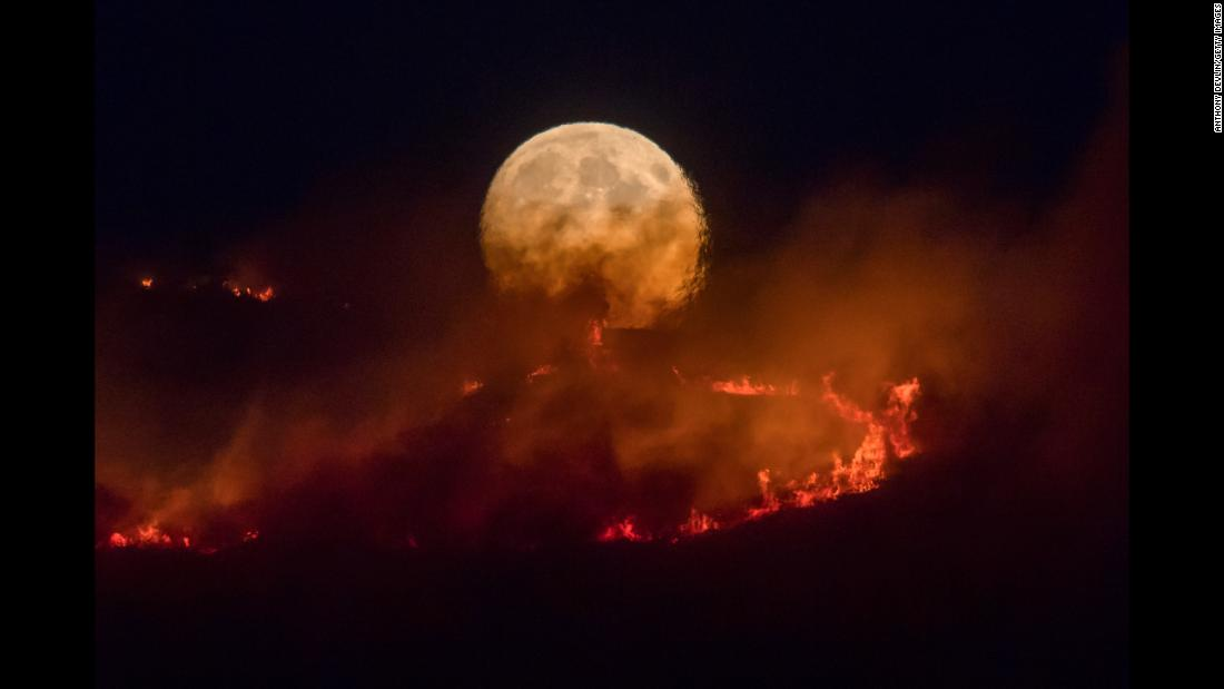 "A full moon rises in Stalybridge, England, as a wildfire sweeps through the region on Tuesday, June 26. <a href=""https://www.cnn.com/2018/06/27/uk/saddleworth-moor-fire-greater-manchester-intl/index.html"" target=""_blank"">The fire</a> has prompted the evacuation of dozens of homes."