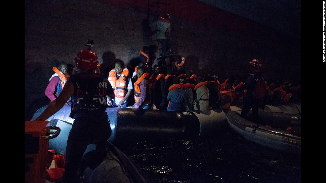 Migrants board a container ship after being rescued from a shipwrecked vessel off the coast of Libya on Friday, June 22. They were trying to cross the Mediterranean Sea to reach Europe, the Libyan navy said.